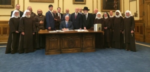 Governor Mike Pence signs Indiana's We Don't Serve Your Kind into law with the approving gaze of the various mullahs, clerics, and militia tribesmen.